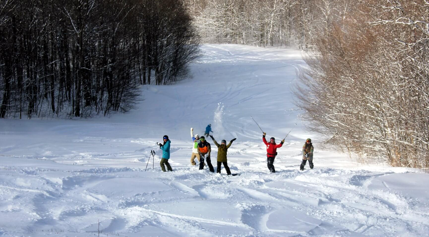 A group of Bolton Valley employees stand in the snow and pose for the camera