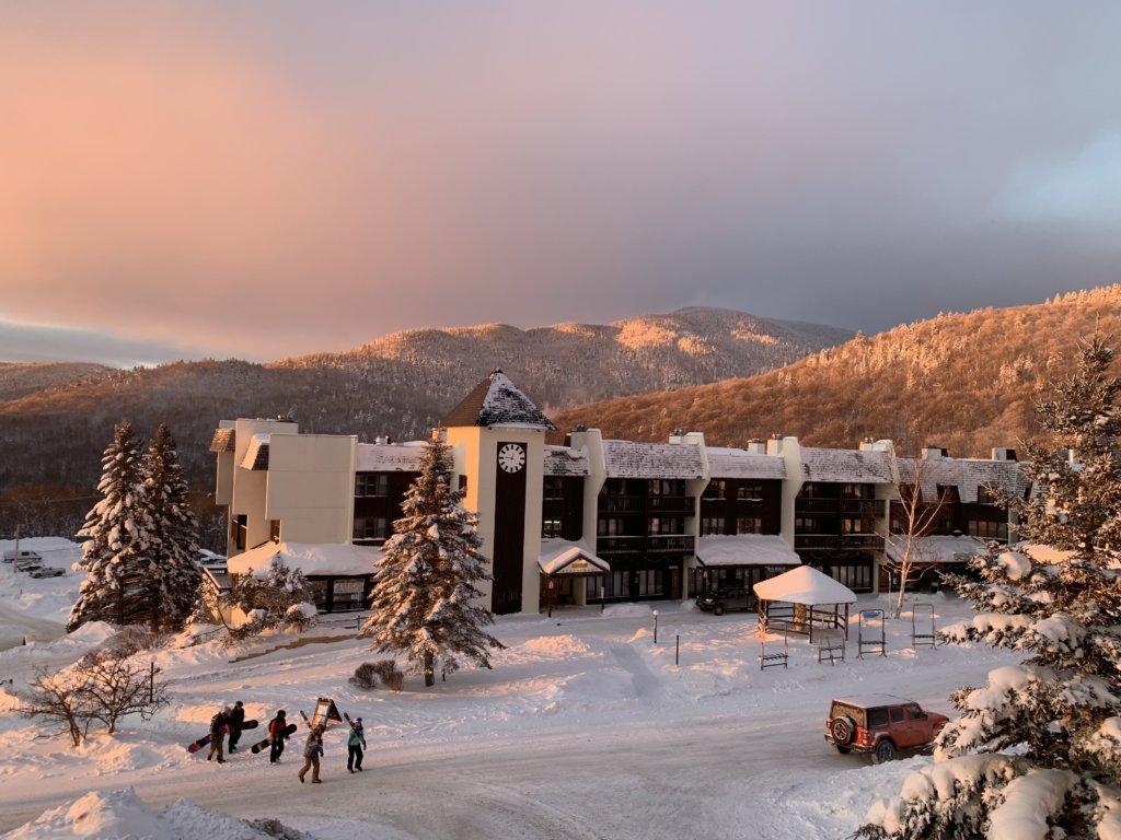 Some Skiers Walking Through The Main Base Village On Their Way To Night Skiing During Sunset